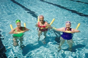 Senior woman swimmers in pool with flotation devices