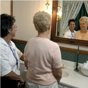 two ladies look in bathroom mirror